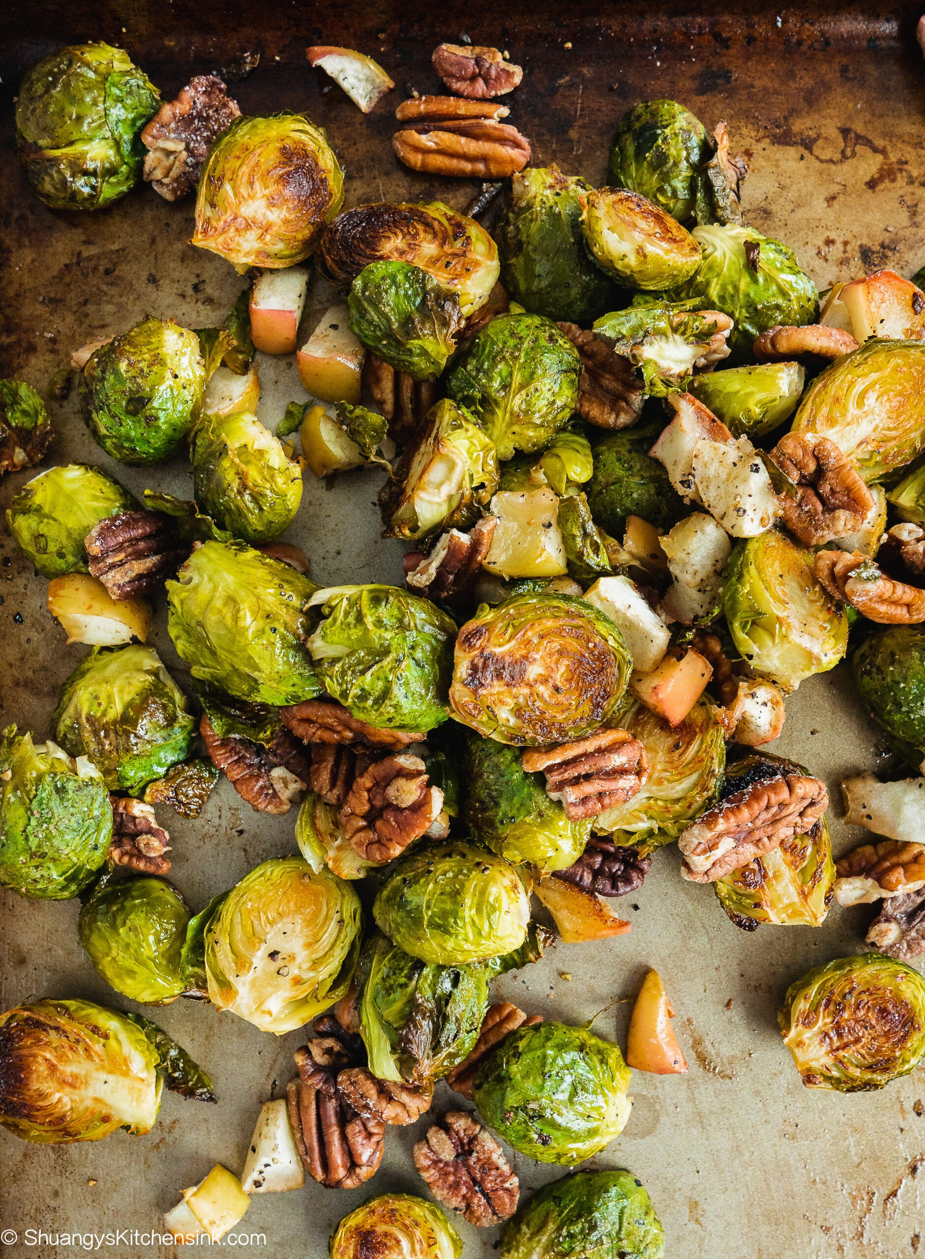 Roasted crispy brussels sprouts with cinnamon apple and toasted pecans on a baking pan fresh out of the oven.