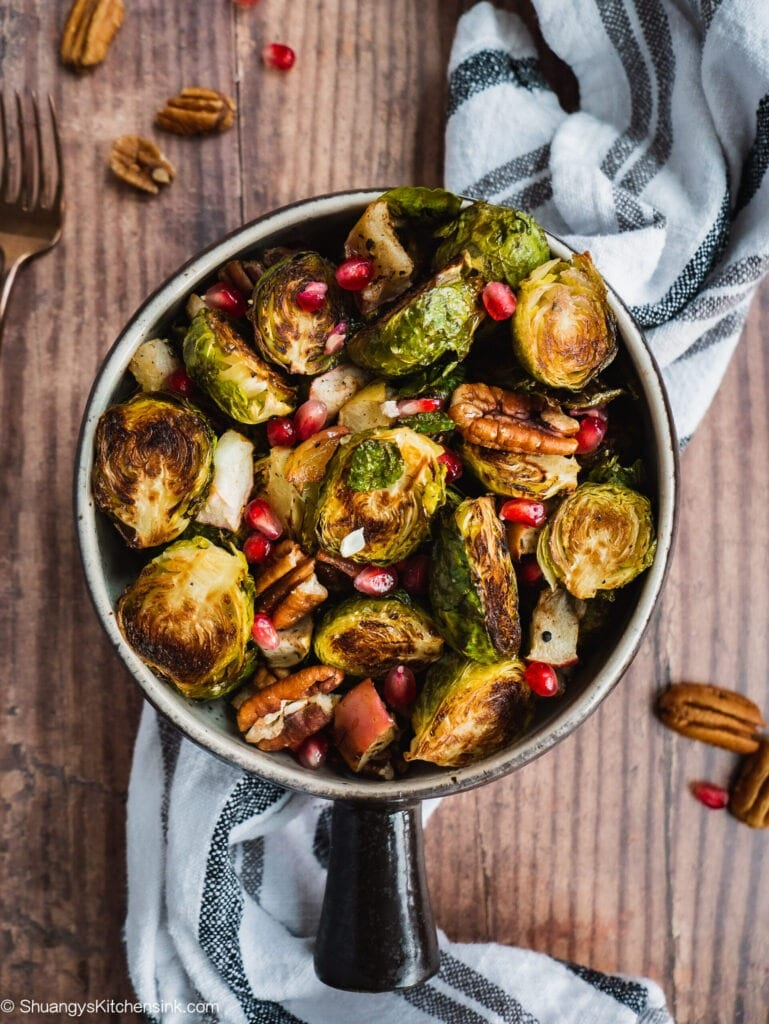 Crispy brussels sprouts with roasted apple and pecans topped with pomegranate seeds in a pot on a wood counter. There is a kitchen towel in the background and pecans.