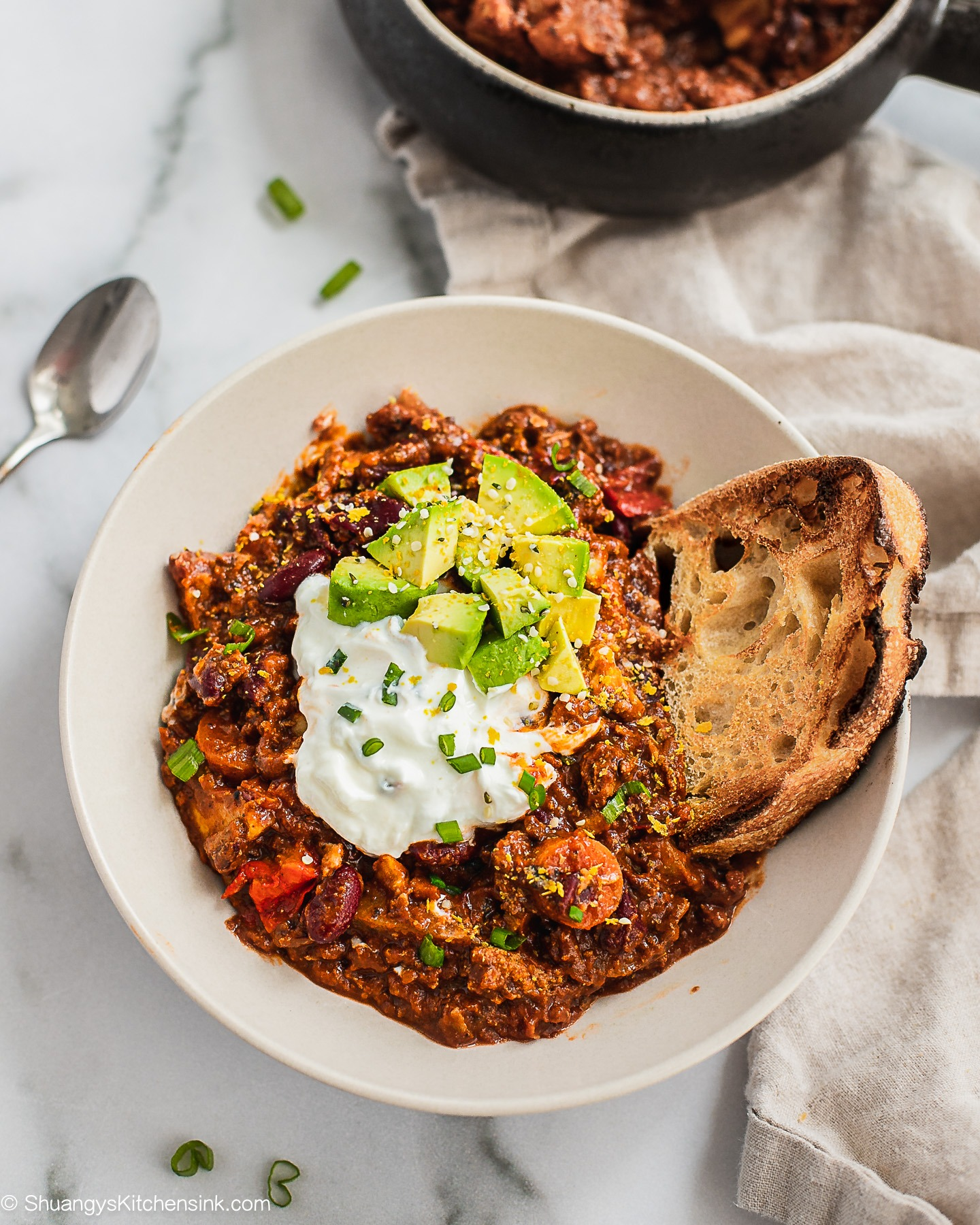 A bowl of sweet potato chili Topped with avocado, yogurt and scallions. There is a piece of toasted crusty bread on the side of the bowl.