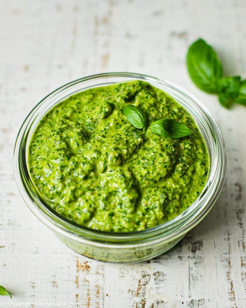 A dish of Vegan nut free pesto. There are a few pieces of basil on the side.
