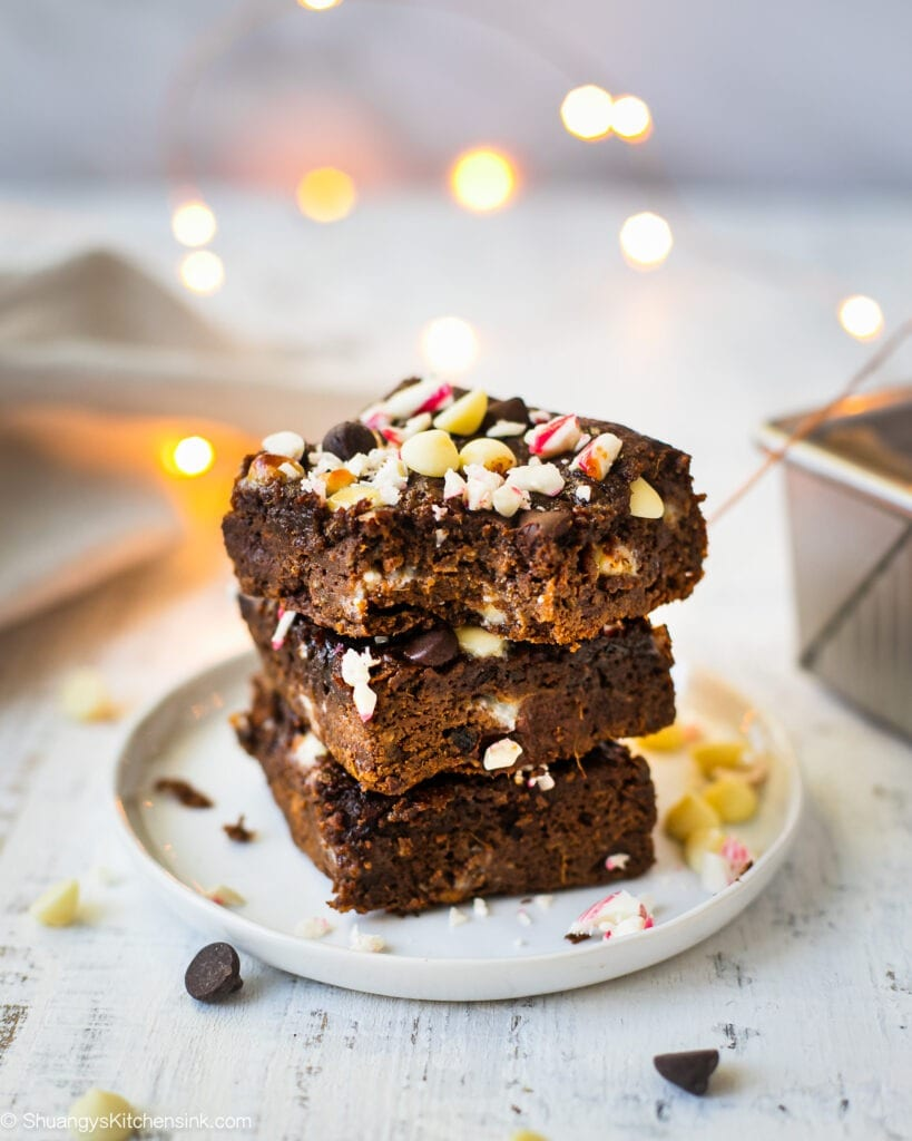 A stack sweet potato peppermint brownie that has candy cane sprinkles on top. There are chocolate chips on the table and Christmas lights in the background.