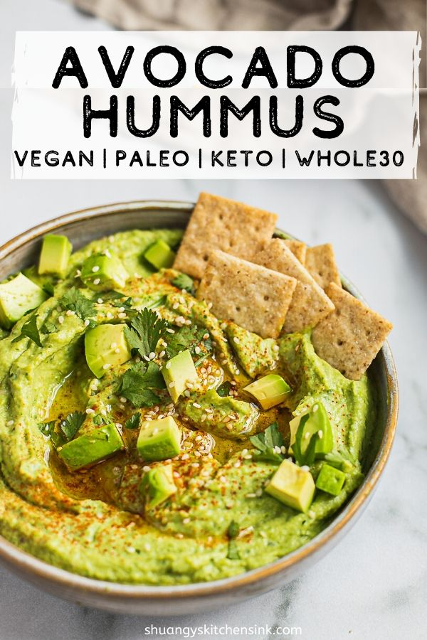 A bowl of paleo vegan avocado hummus and crackers. There are avocado cubes and cilantro on top.