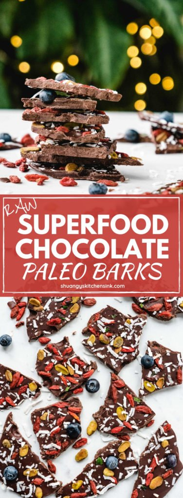 The vegan superfood chocolate bark is broken into pieces that are stacked on top of each other. There are blueberries and goji berries on the table as well. There are also nuts and shaved coconut.