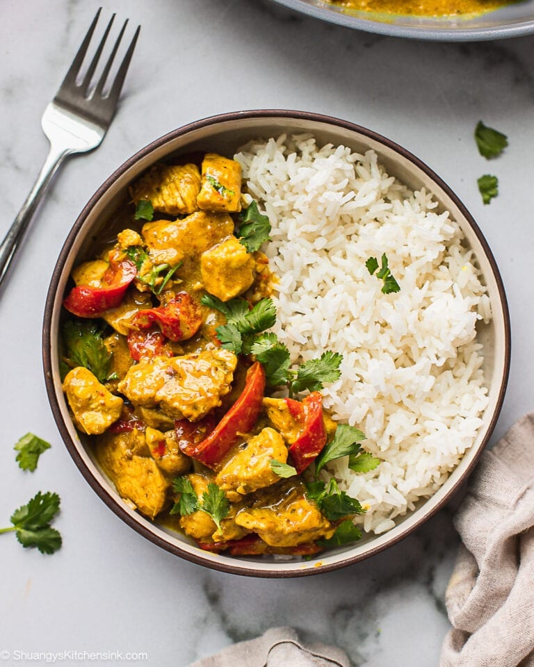 A bowl of jasmine rice and Thai Coconut Curry Chicken. There is a fork on the side.