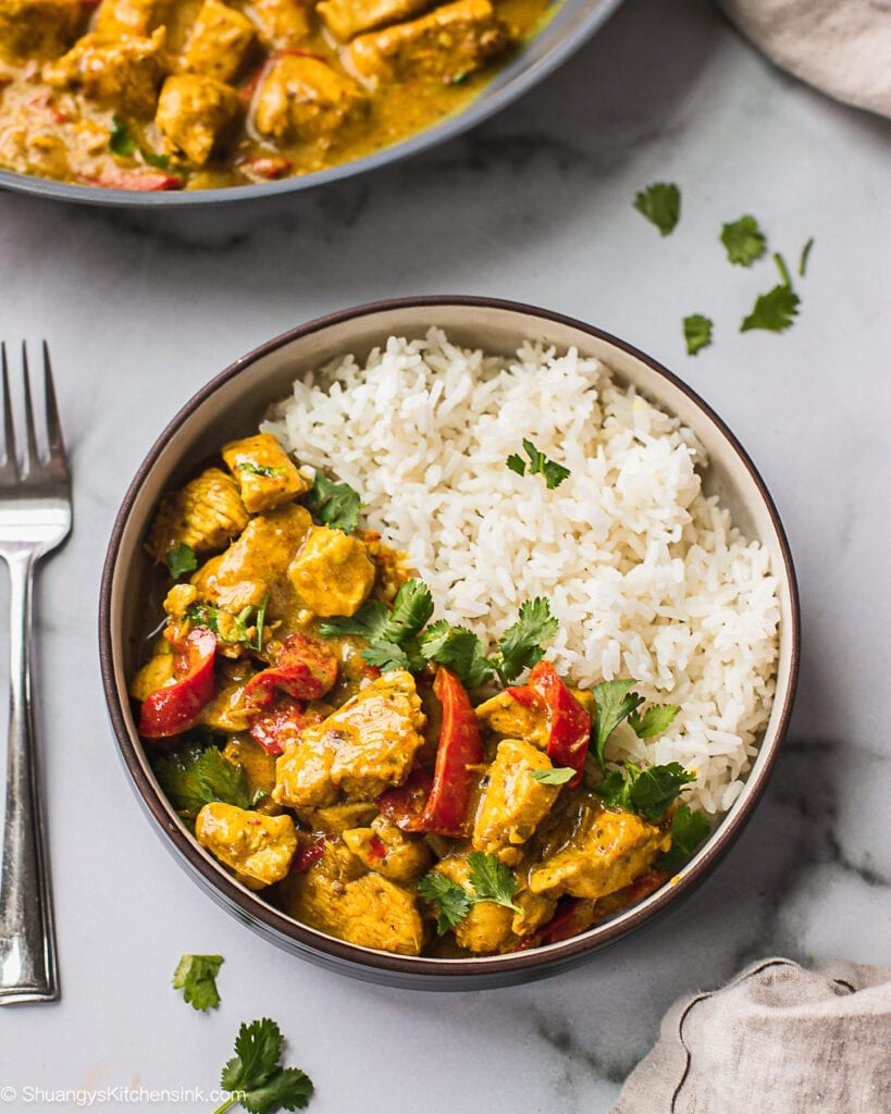 A bowl of jasmine rice and Thai Coconut Curry Chicken. There is a fork on the side. This is a great freezer meal for new moms