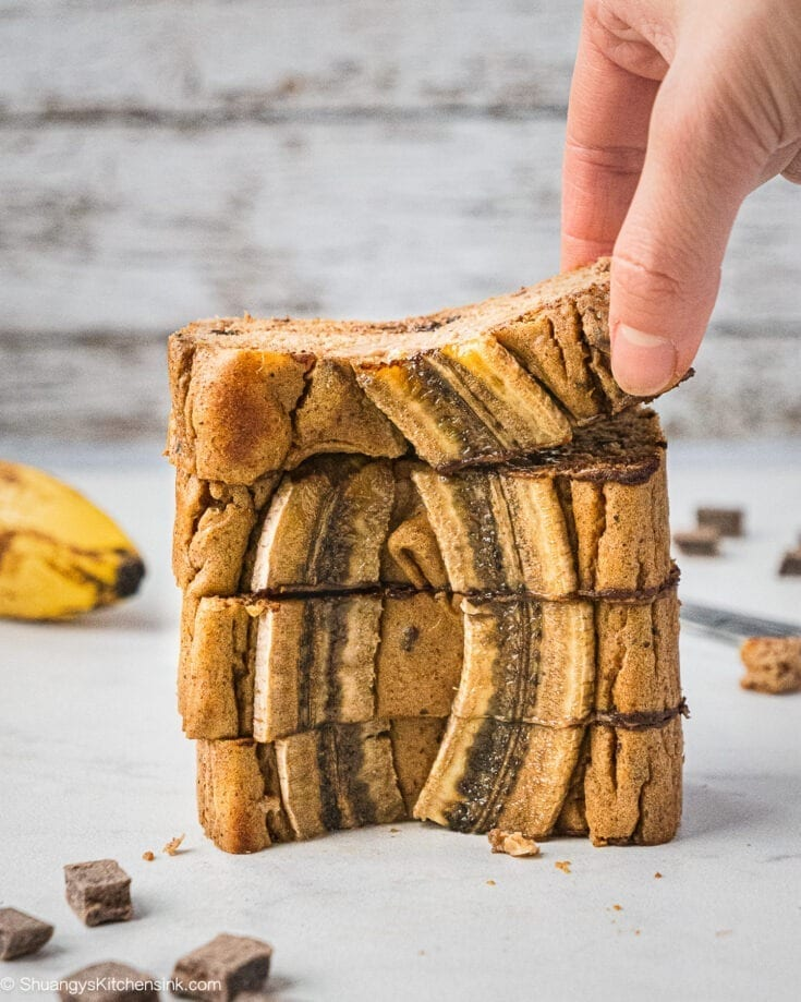 A stack of 4 pieces of banana bread with two pieces of sliced bananas on top. There is a hand grabbing one.