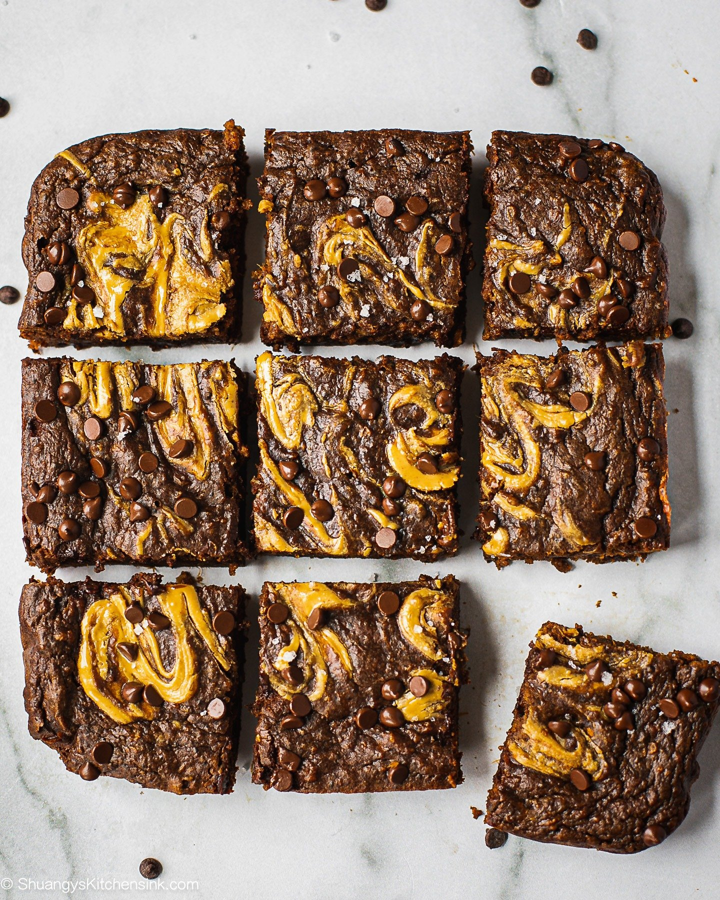 9 pieces of sweet potato paleo brownies with almond butter swirl and chocolate chips on top.