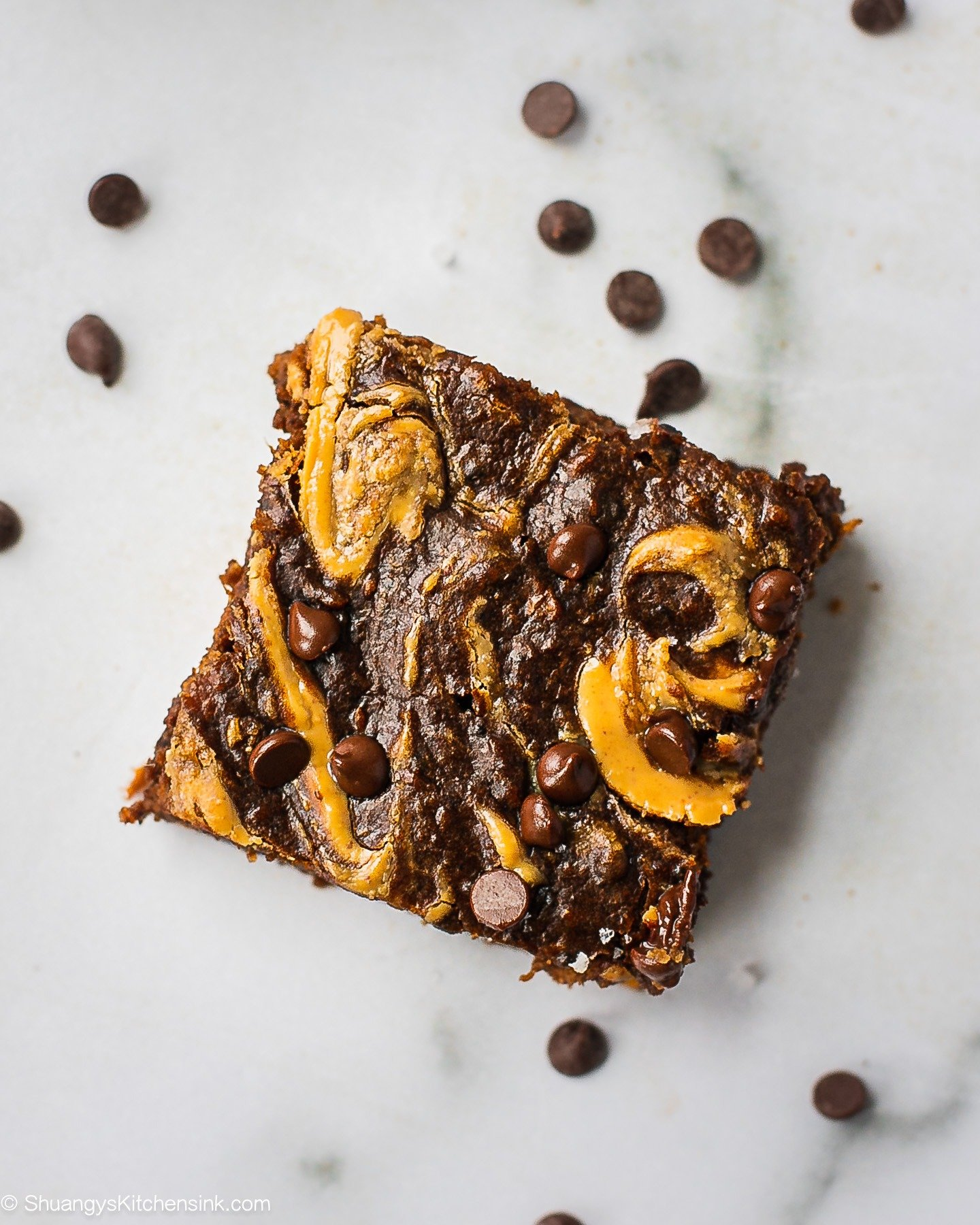 A square of sweet potato brownie. There is an orange swirl on top and some chocolate chips sprinkled on top of the healthy dessert
