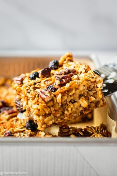 A spatula is serving a piece of freshly baked carrot cake oatmeal bars. This gluten free vegan carrot cake appears to be soft and chewy, perfect for Easter brunch.