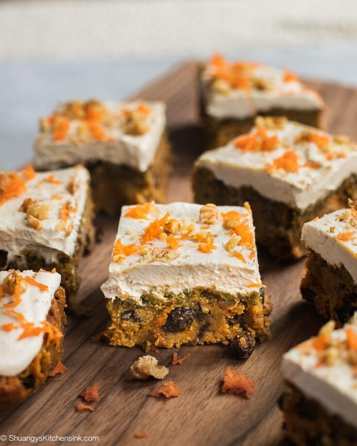 A freshly baked carrot cake cut into squares topped with cashew cream cheese frosting and sprinkle of fresh carrots, and walnuts.