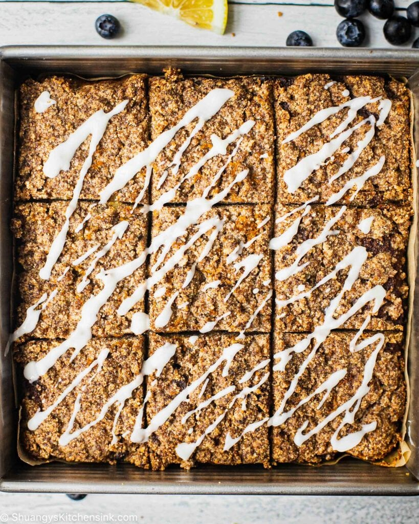 There is a gluten-free cake in a loaf pan. The healthy dessert is cut into 9 squares. The cake is drizzled with a maple coconut butter.