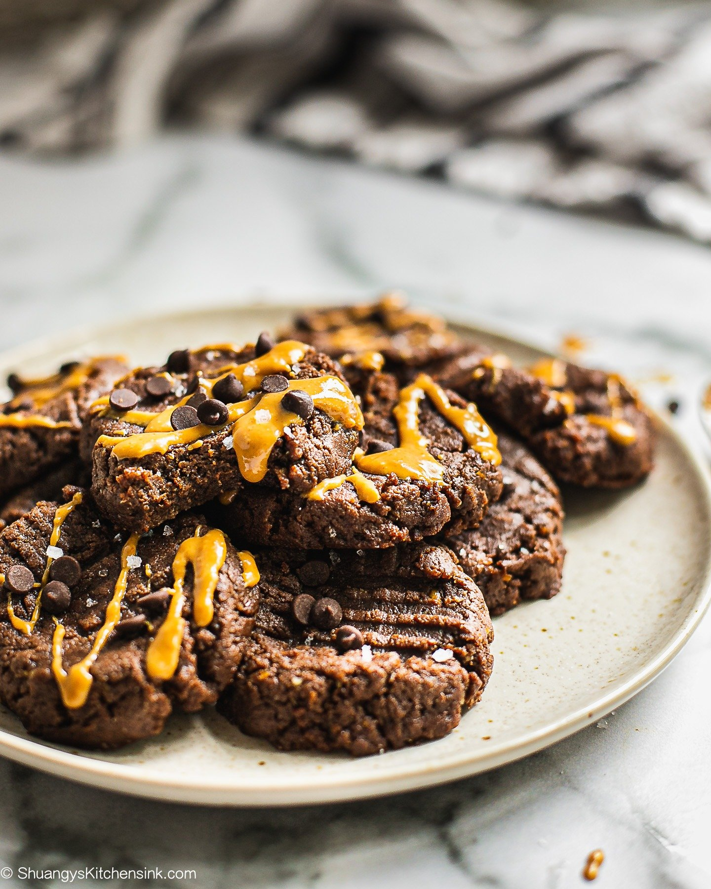 A plate of no bake double chocolate cookies. There are some peanut butter and chocolate chips on top.