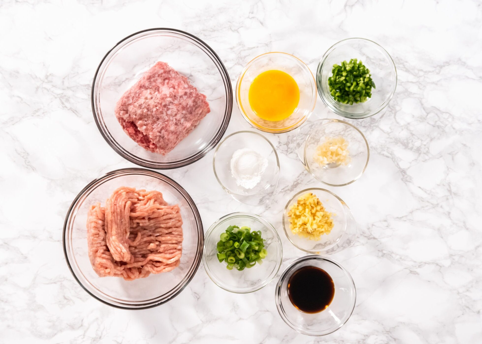 Ingredients needed to make the best healthy asian meatballs. There are ground chicken, ground pork, egg, scallions, ginger, garlic, coconut aminos and vinegar.