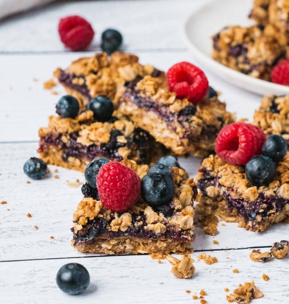 Healthy Blueberry crumble bars topped with fresh blueberries and raspberries