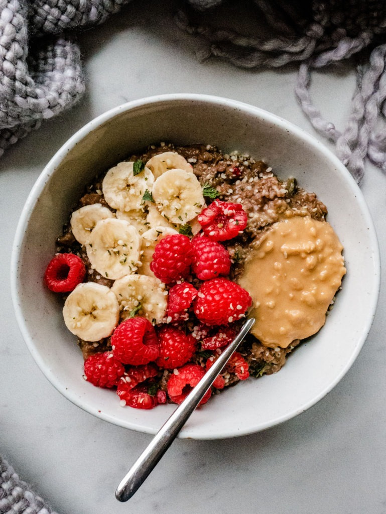 A large bowl of chocolate overnight oats topped with peanut butter, banana slices, fresh raspberries and a sprinkle of hemp seeds.