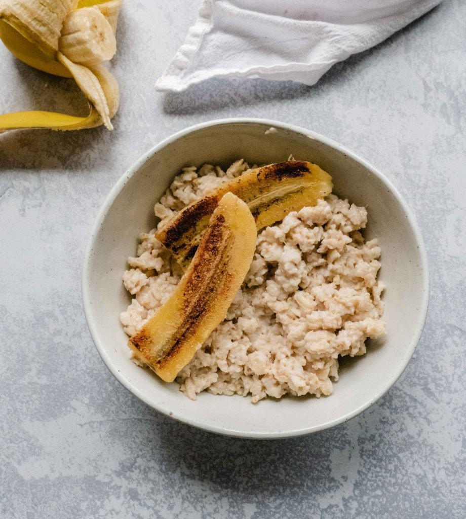 On a breakfast table there is a bowl of creamy overnight oatmeal topped with half a caramelized banana. There is also half a banana still in its peel on the side of the bowl.