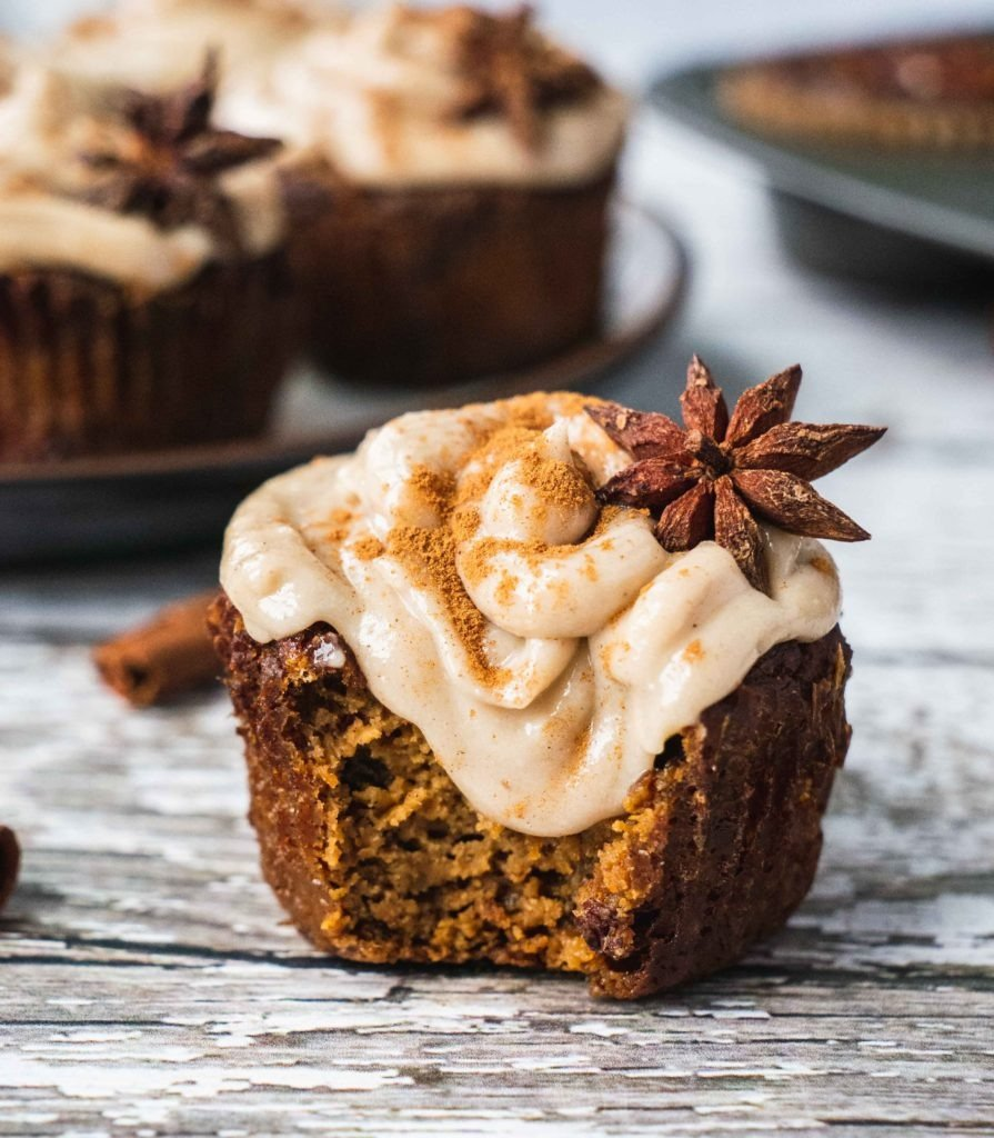 There is a paleo morning glory muffin with raisins and pecans, topped with a cashew frosting. on top of the icing there is a star anis and a sprinkle of cinnamon.