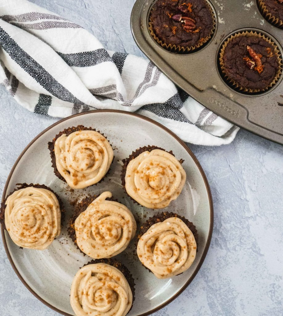 There is a plate full of grain-free breakfast cupcakes with a creamy dairy-free frosting. Next to it there are gluten-free muffins with pecans, carrots and ginger