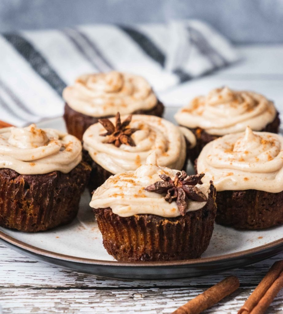 There are healthy, suger-free, paleo muffins frosted with vegan creamy icing. There are cinnamon and star anis in the batter and as a decoration