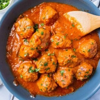Paleo Italian Meatballs with Creamy Tomato Sauce with a wooden spoon in the pan and fresh basil sprinkled on top