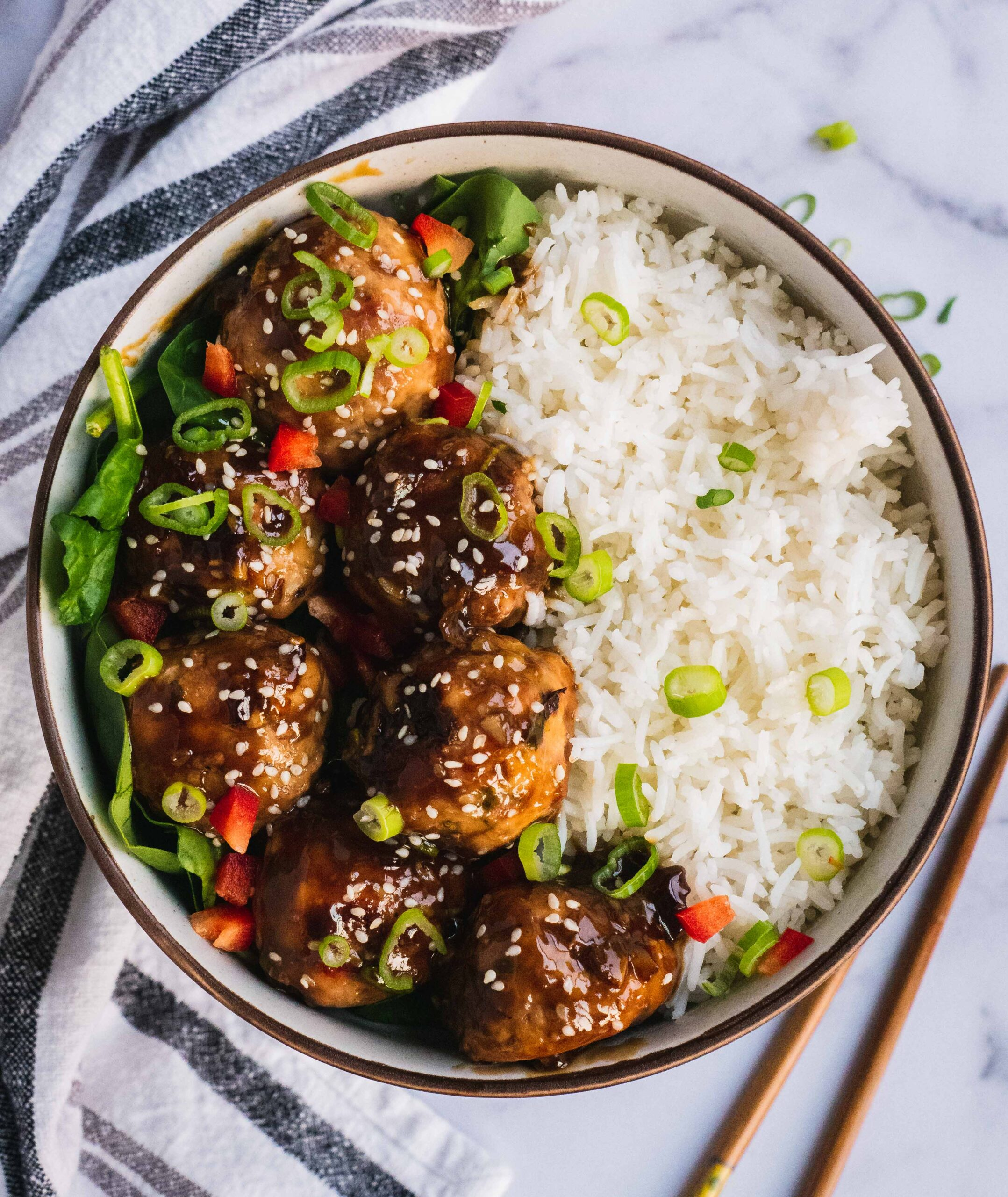 A bowl of sticky asian meatballs served with jasmine rice. The dish is topped off with scallions and some red pepper flakes.