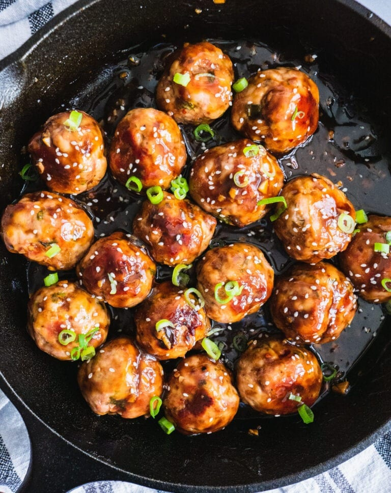 A cast iron pan of whole30 sticky asian meatballs in Asian sticky sauce. There are scallions and sesame seeds on top.