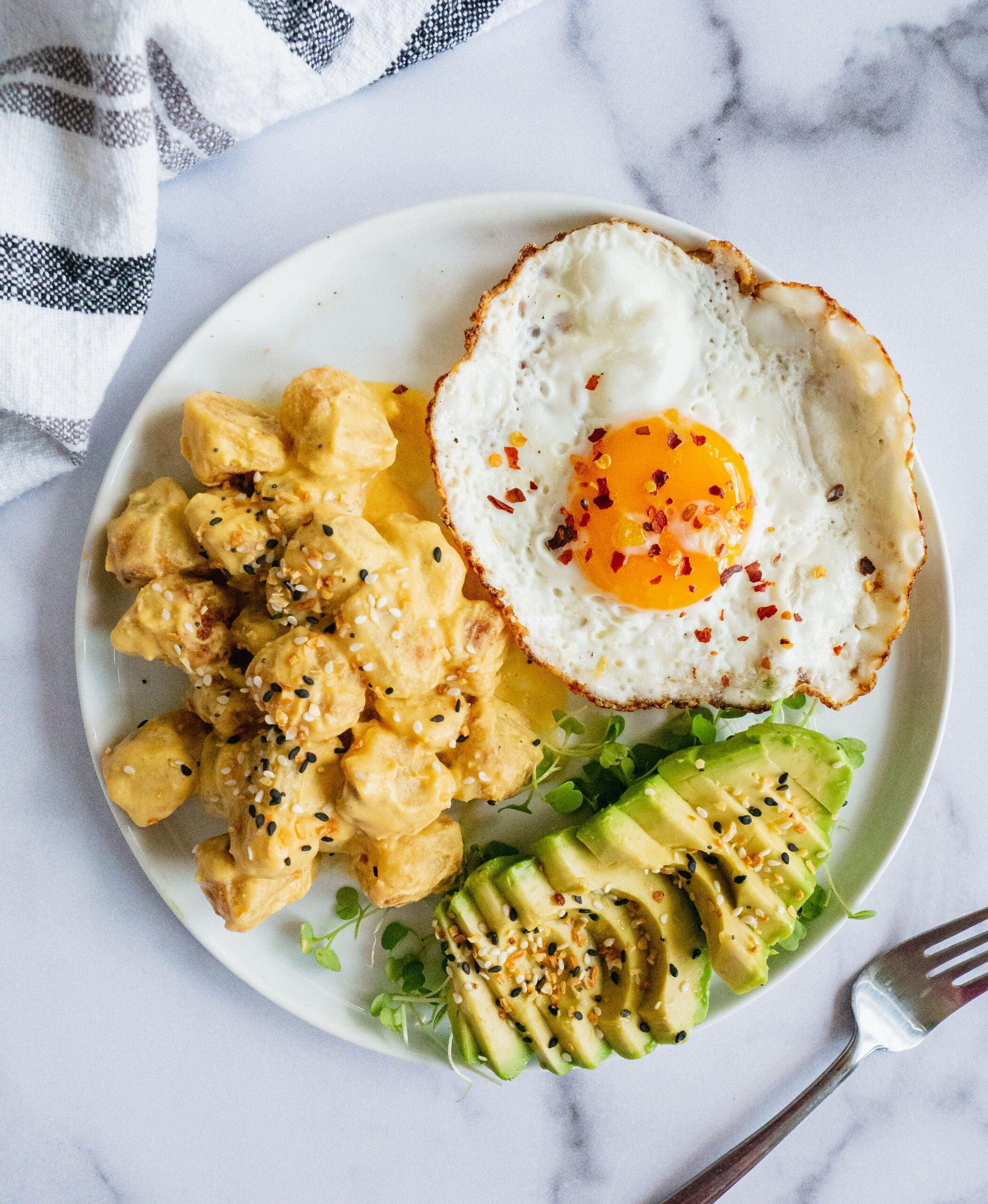 A plate of breakfast food. There is a fried egg with chili flakes, a sliced avocado and vegan cheese sauce