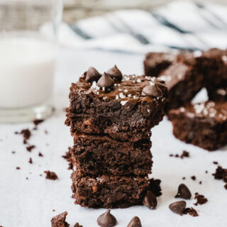 Fudgy Gooey Healthy Brownies stacked up with more brownies and a glass of milk.
