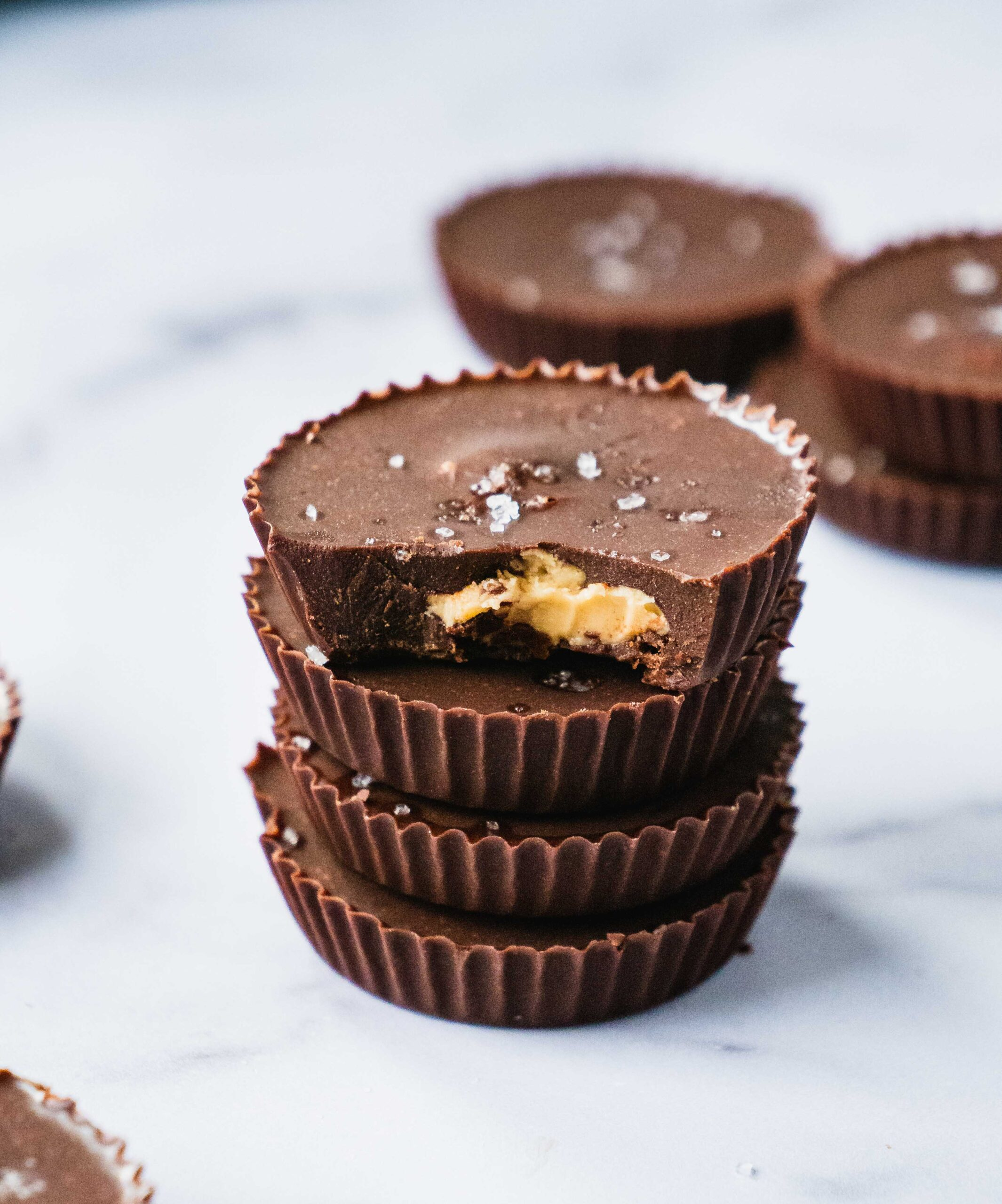 four snack bite sized peanut butter cups stacked on each other. They are sprinkled with sea salt