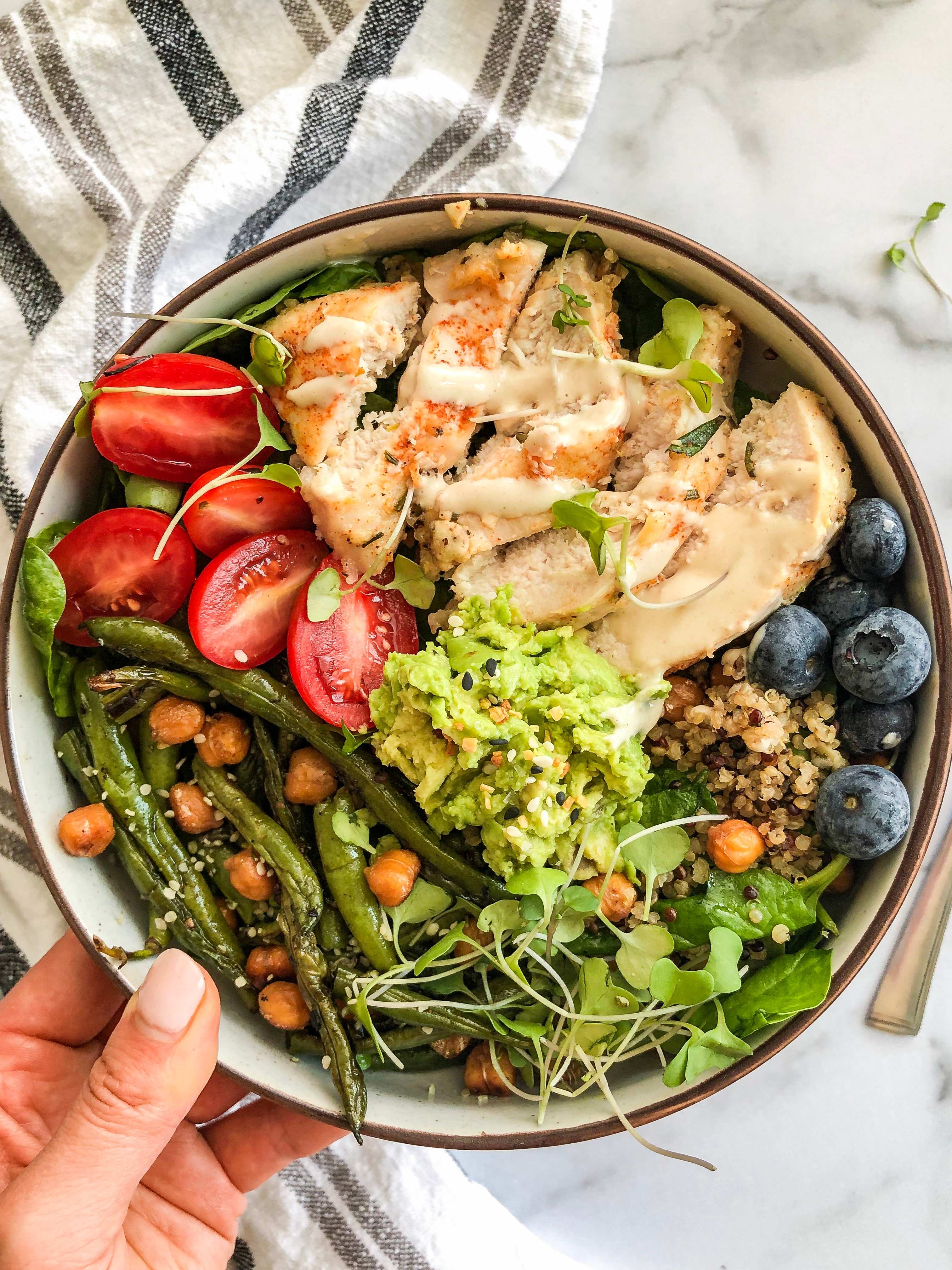 A bowl with green beans, tomatoes, avocado, quinoa, blueberries and white meat. There is salad in the bottom as well and chickpeas are sprinkled on top.