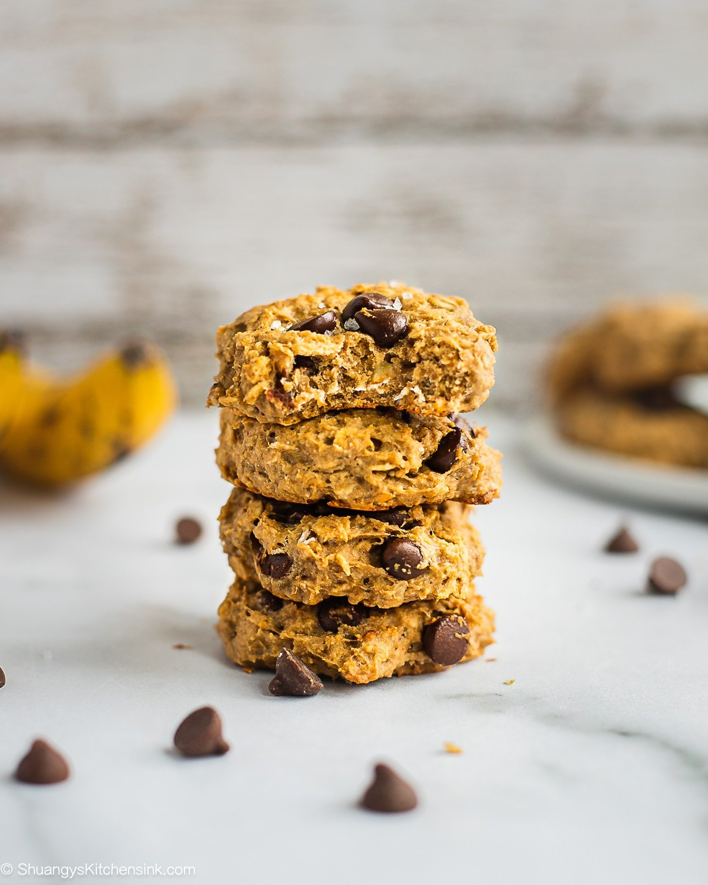 A stack of peanut butter banana oatmeal cookies. There are some chocolate chips on the table.
