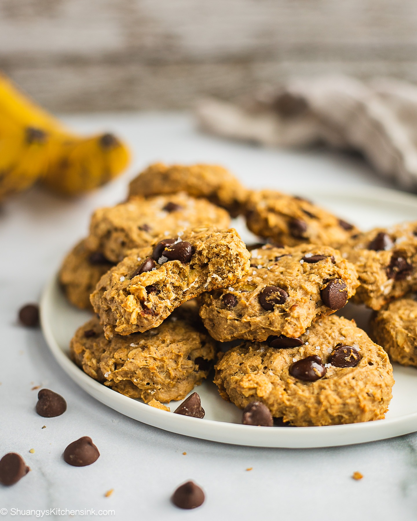 A plate of soft cookies made from oats and fruits. In the background there are bananas and chocolate chips