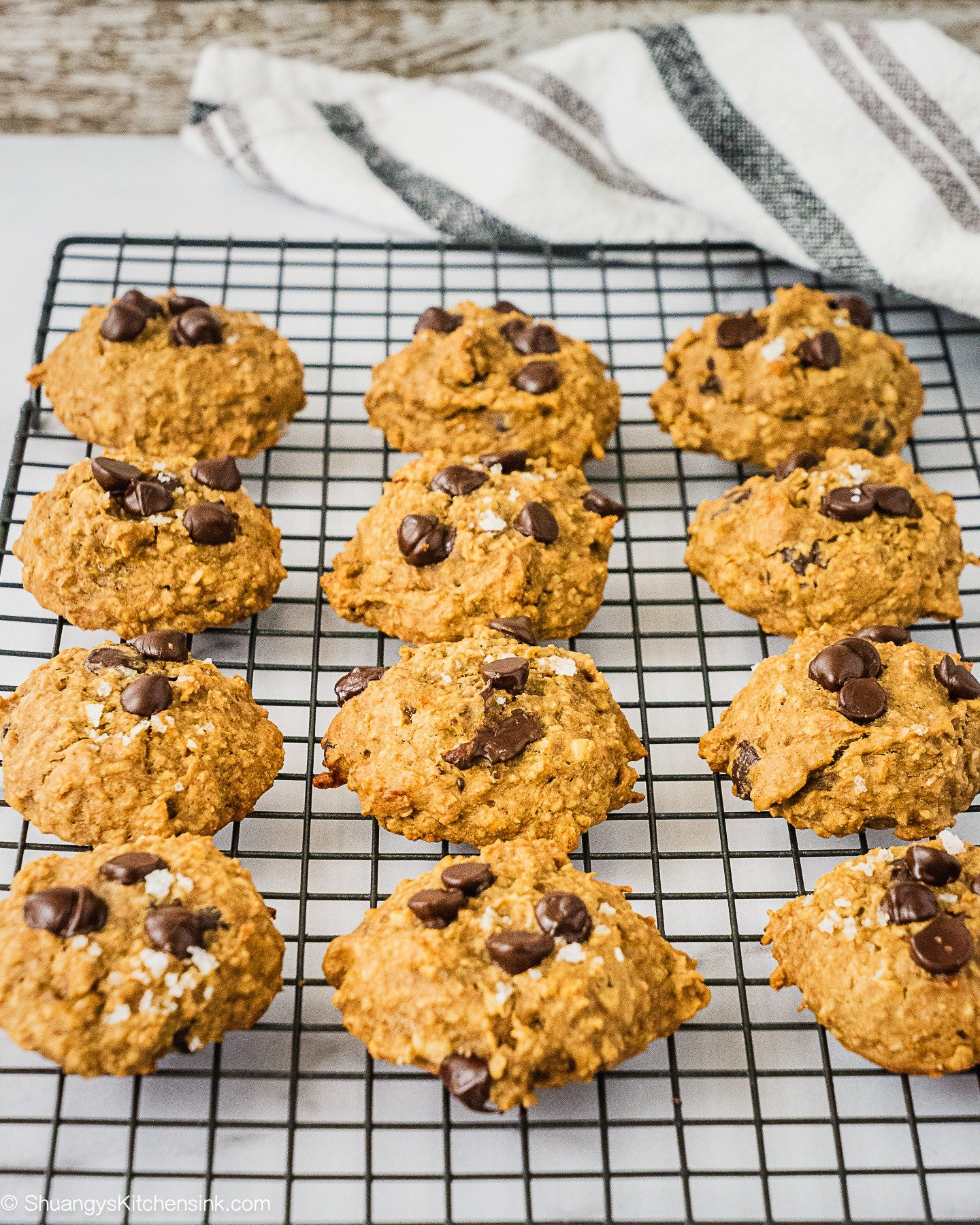 A batch of freshly baked peanut butter banana oatmeal cookies on a cooling rack.