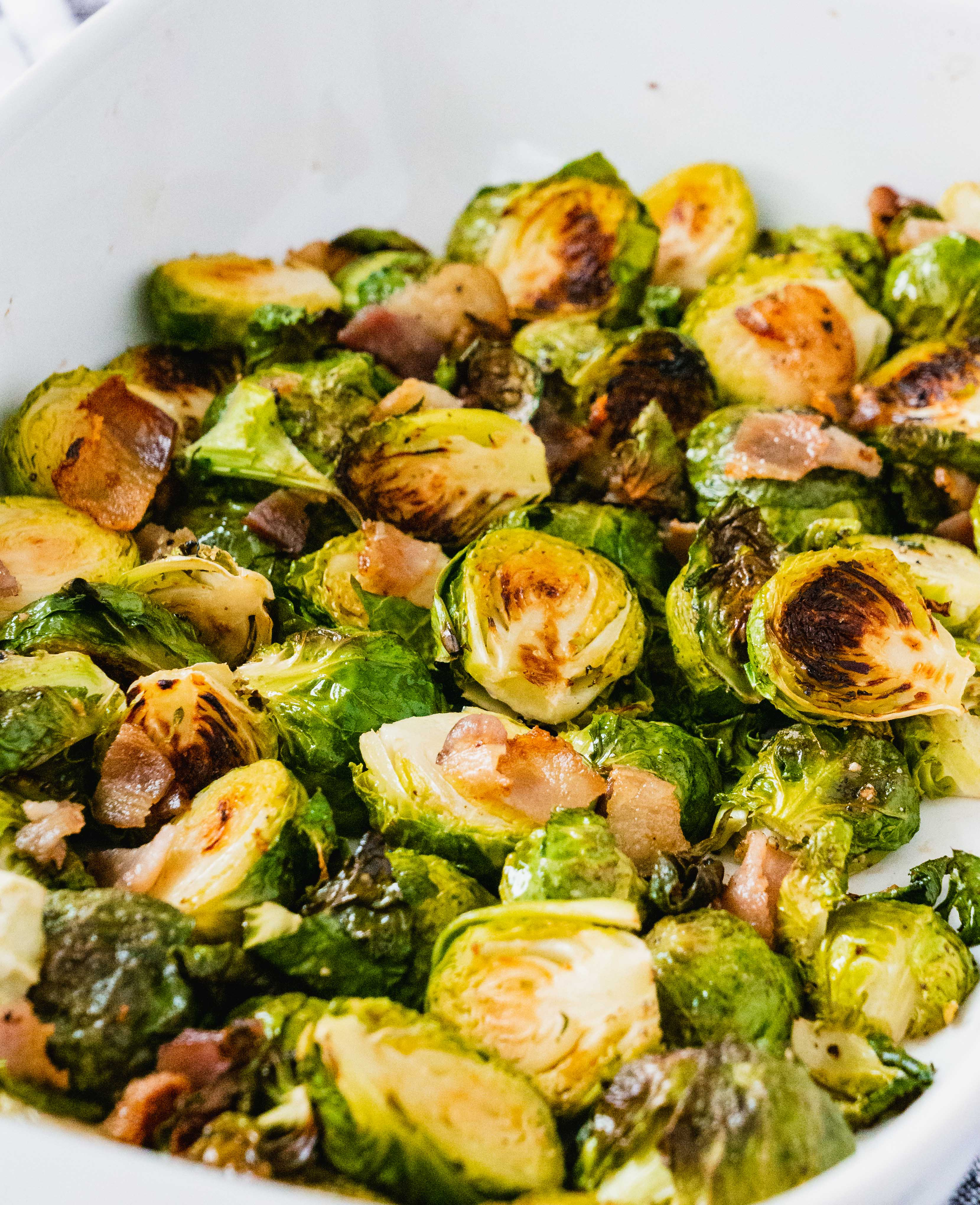 Oven baked Crispy Bacon Brussel Sprouts | These oven roasted crispy bacon brussels sprouts are so delicious and flavorful. They are also incredibly easy to make under 20 minutes. Even better? This healthy recipe is paleo and whole 30 compliant. Perfect Thanksgiving or Christmas Side dish that are tasty and healthy. | #thanksgiving #brusselsprouts #bacon #whole30 #paleo #lowcarb #glutenfree #healthyrecipe