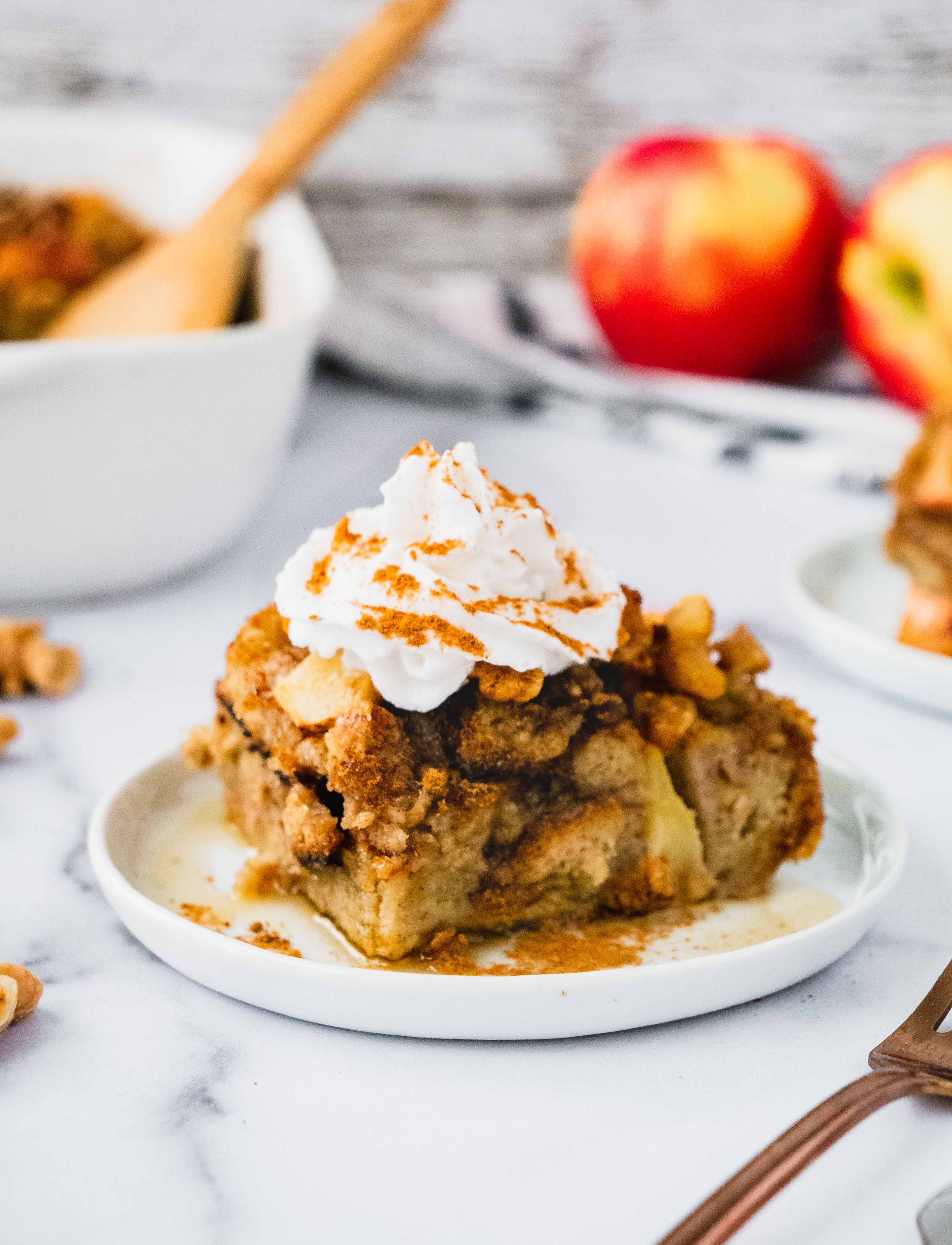 A slice of Apple Pie French Toast Casserole topped with whipped cream and cinnamon sugar. Additionally, drizzled with warm maple syrup