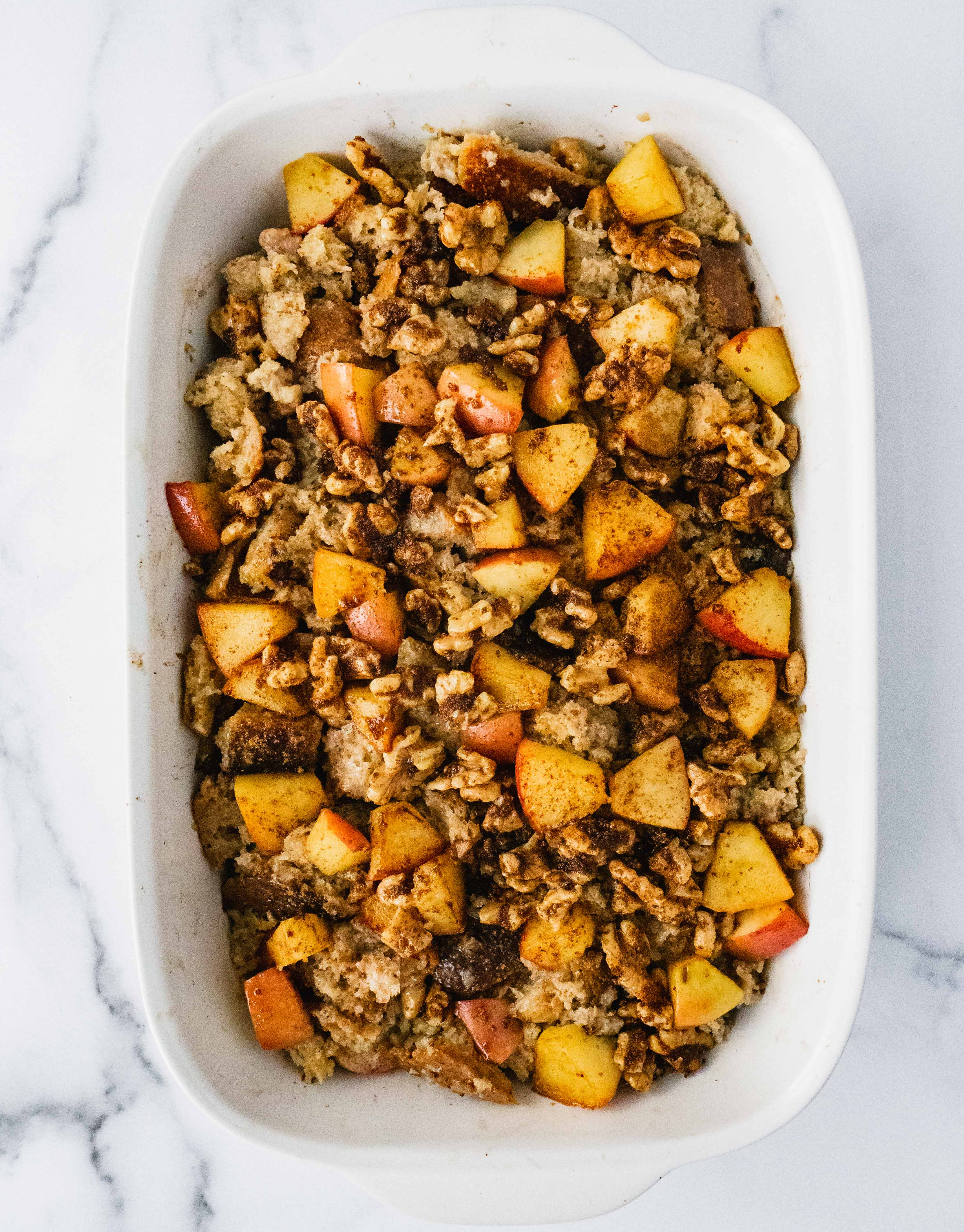 A pan of baked french toast casserole topped with sautted cinnamon apples