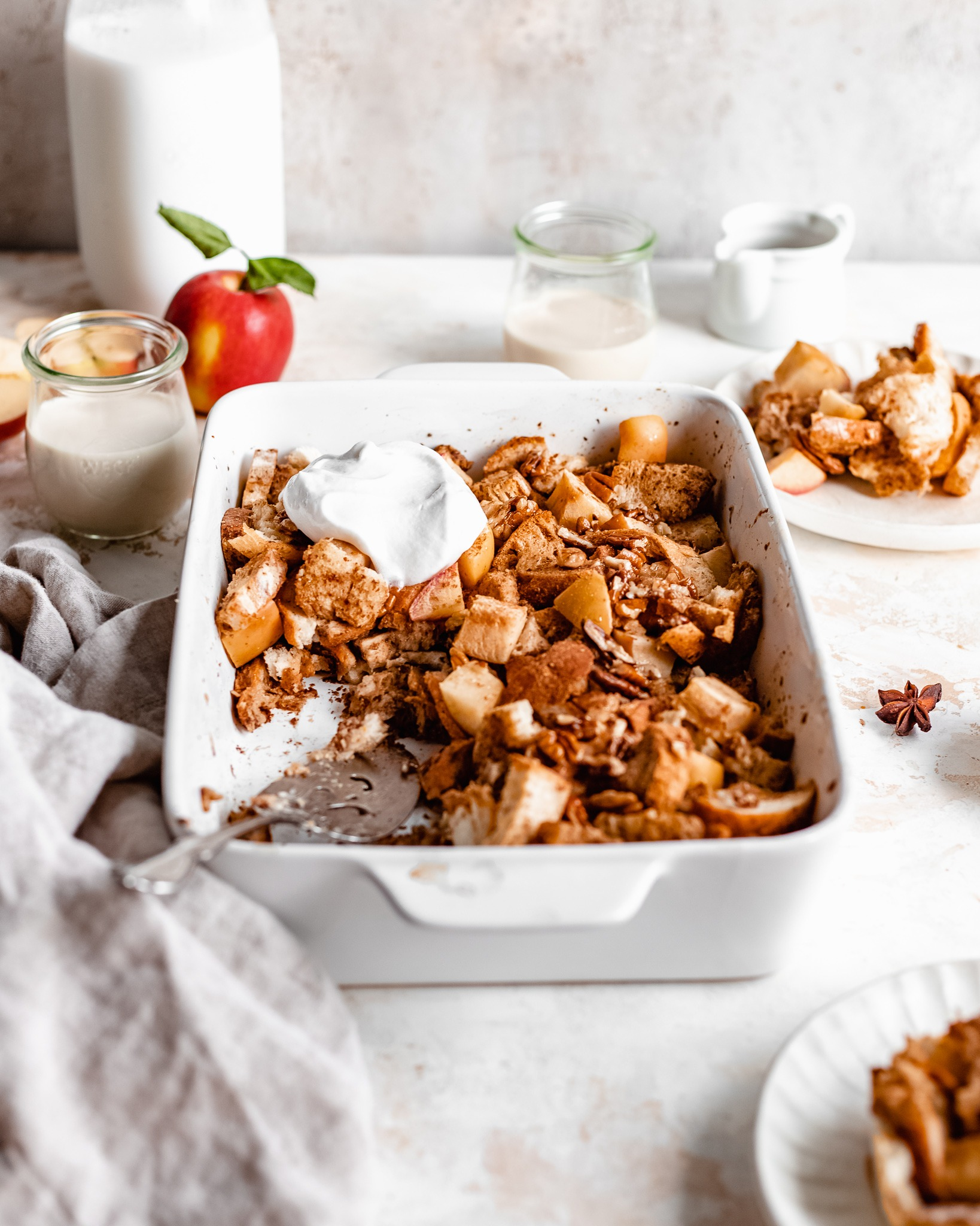 A pan of warm and fresh oven baked french toast. There are cinnamon apple and candied walnuts on the tray. Topped with a scoop of coconut cream, this apple french toast casserole is ready to be served with a big serving spoon.