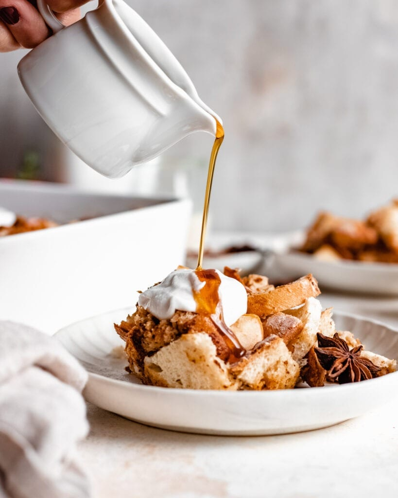 A plate of a apple french toast casserole that is served with coconut cream, candied walnuts and cinnamon apples. This overnight french toast casserole appears to be soft and crunchy. There is maple syrup pouring over the french toast.