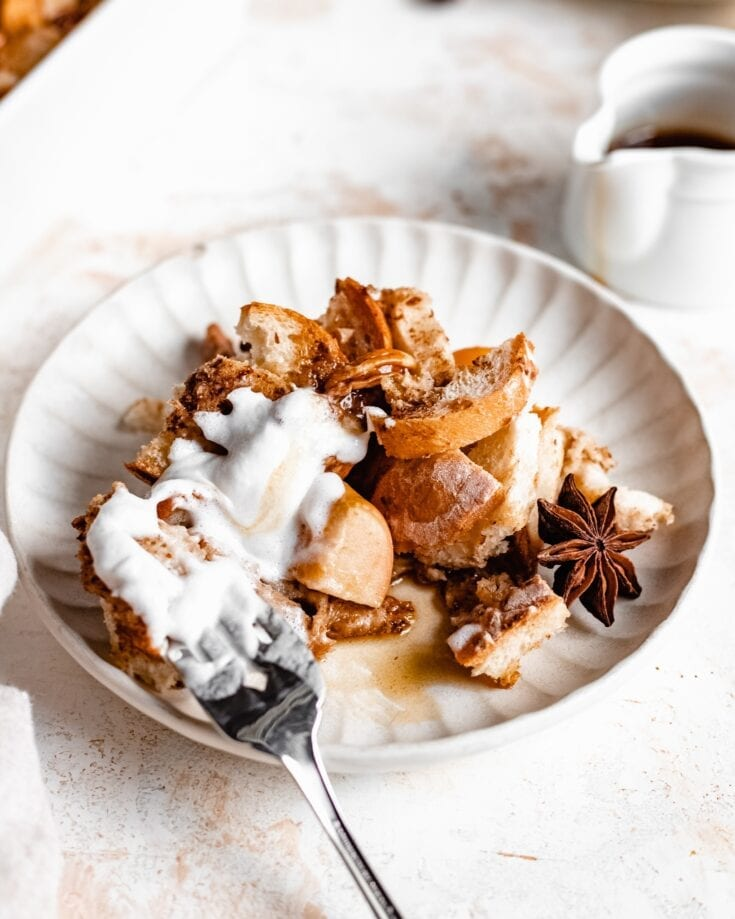 A plate of a apple french toast casserole that is served with coconut cream, candied walnuts and cinnamon apples. This overnight french toast casserole appears to be soft and crunchy.