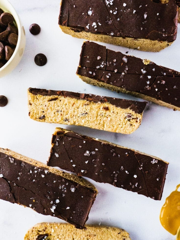 No Bake Chocolate Chip Cookie Dough Bars |Gooey and Sweet Chocolate Chip Cookie Dough layered with dark chocolate and sprinkles of sea salt on a piece of marble.