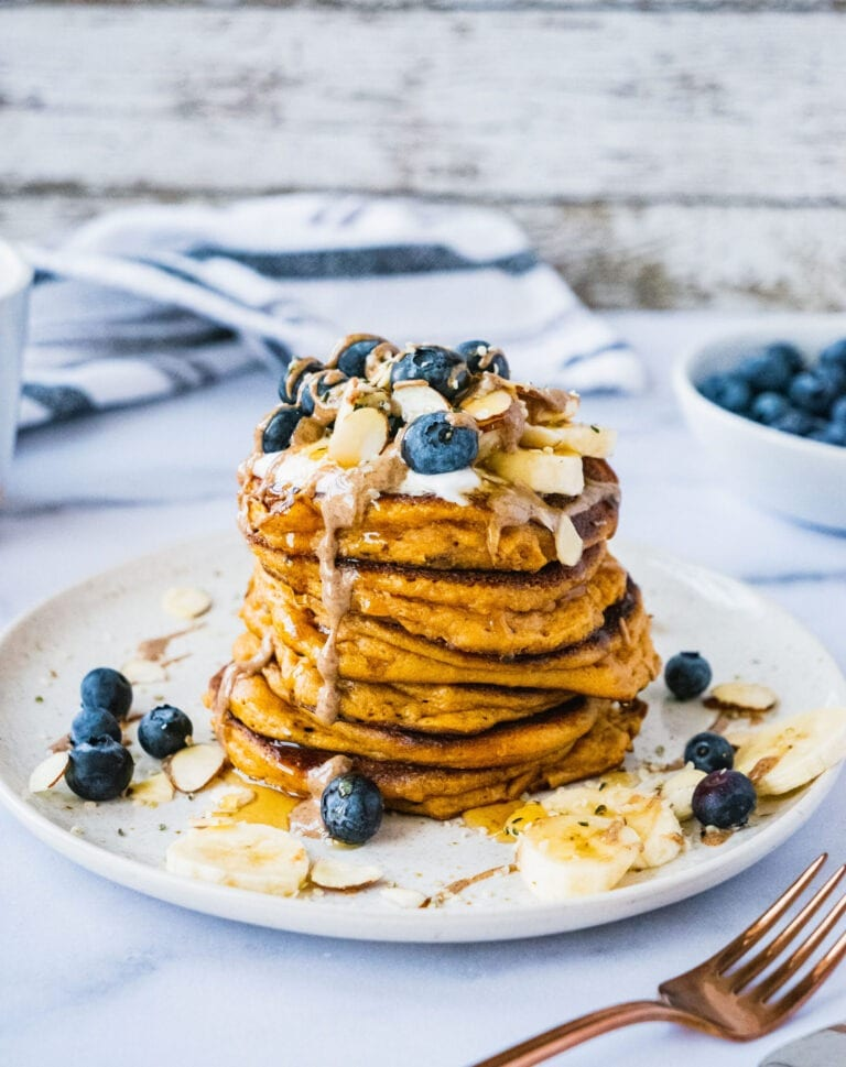 almond flour pancakes topped with blueberry banana, almonds, nut butter and maple syrup.