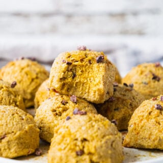 A plate of pumpkin spice energy balls. One of the fat bombs has a bite. The texture is gooey and soft.