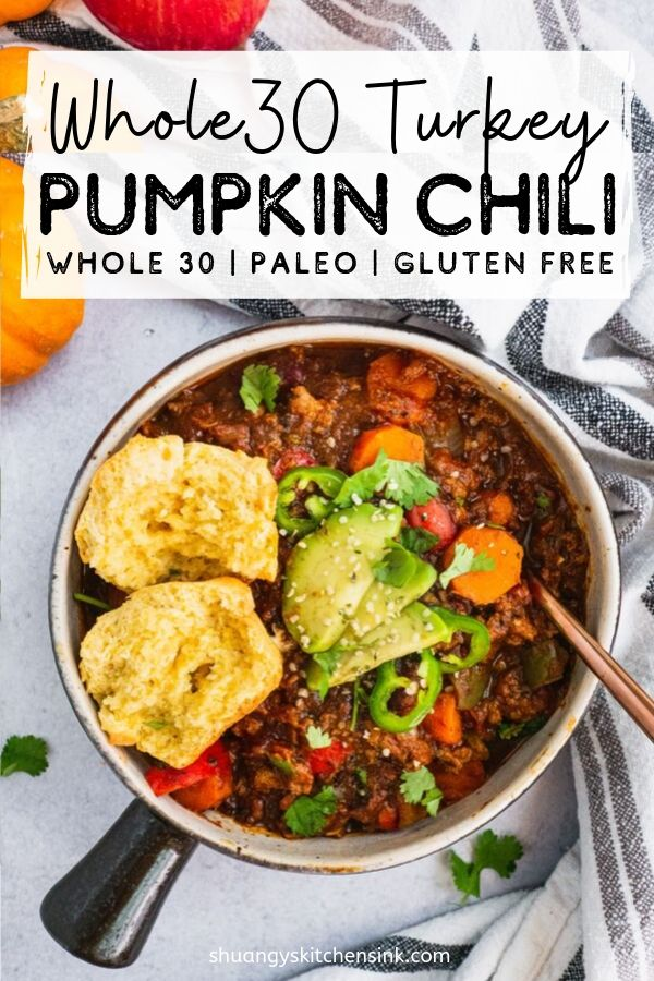 A serving pot with creamy pumpkin turkey chili. Topped with avocado, cilantro, avocado and one corn bread muffin split in half. Pinterest Image