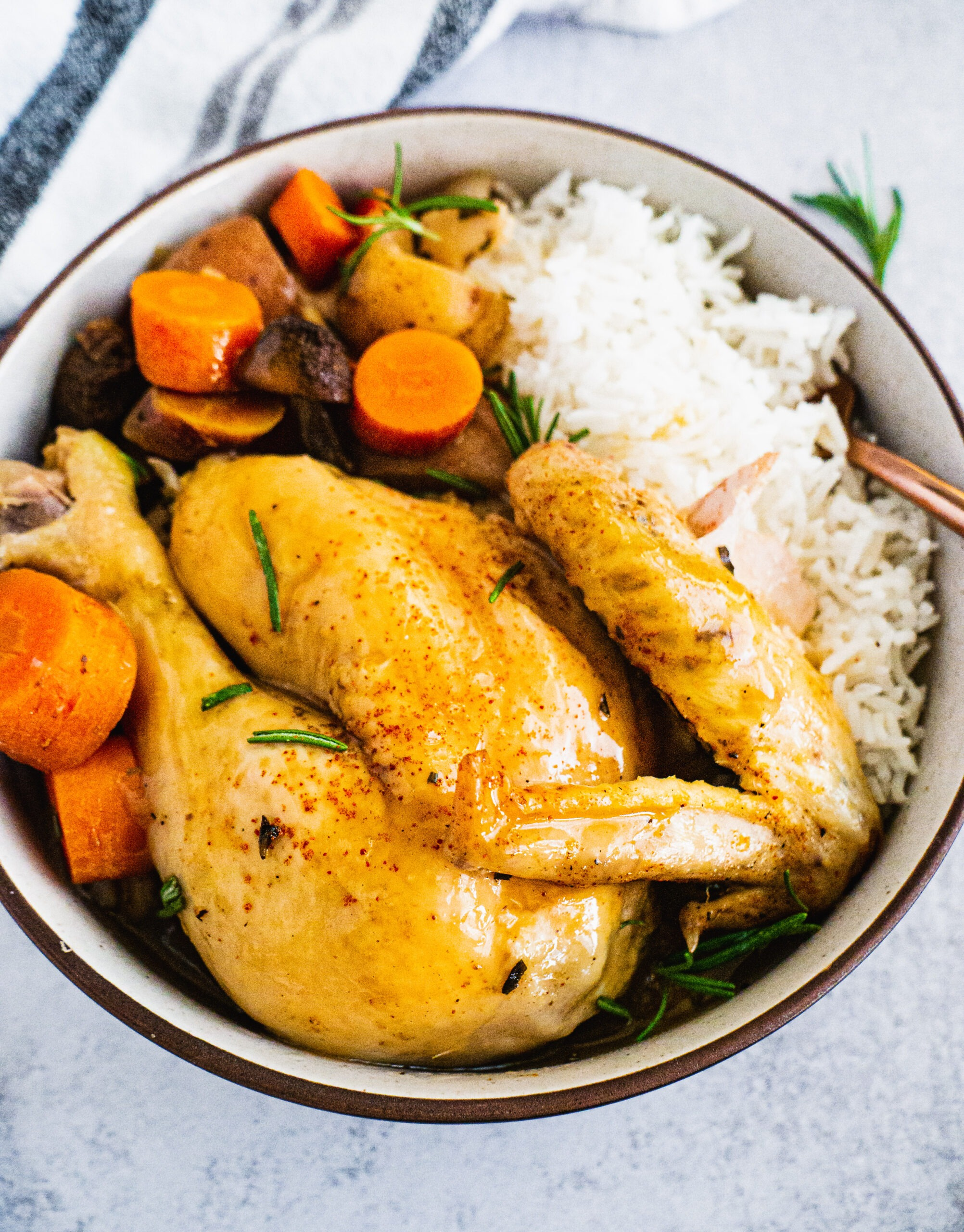 Slow Cooker Chicken in a bowl with vegetables, potatoes and rice.