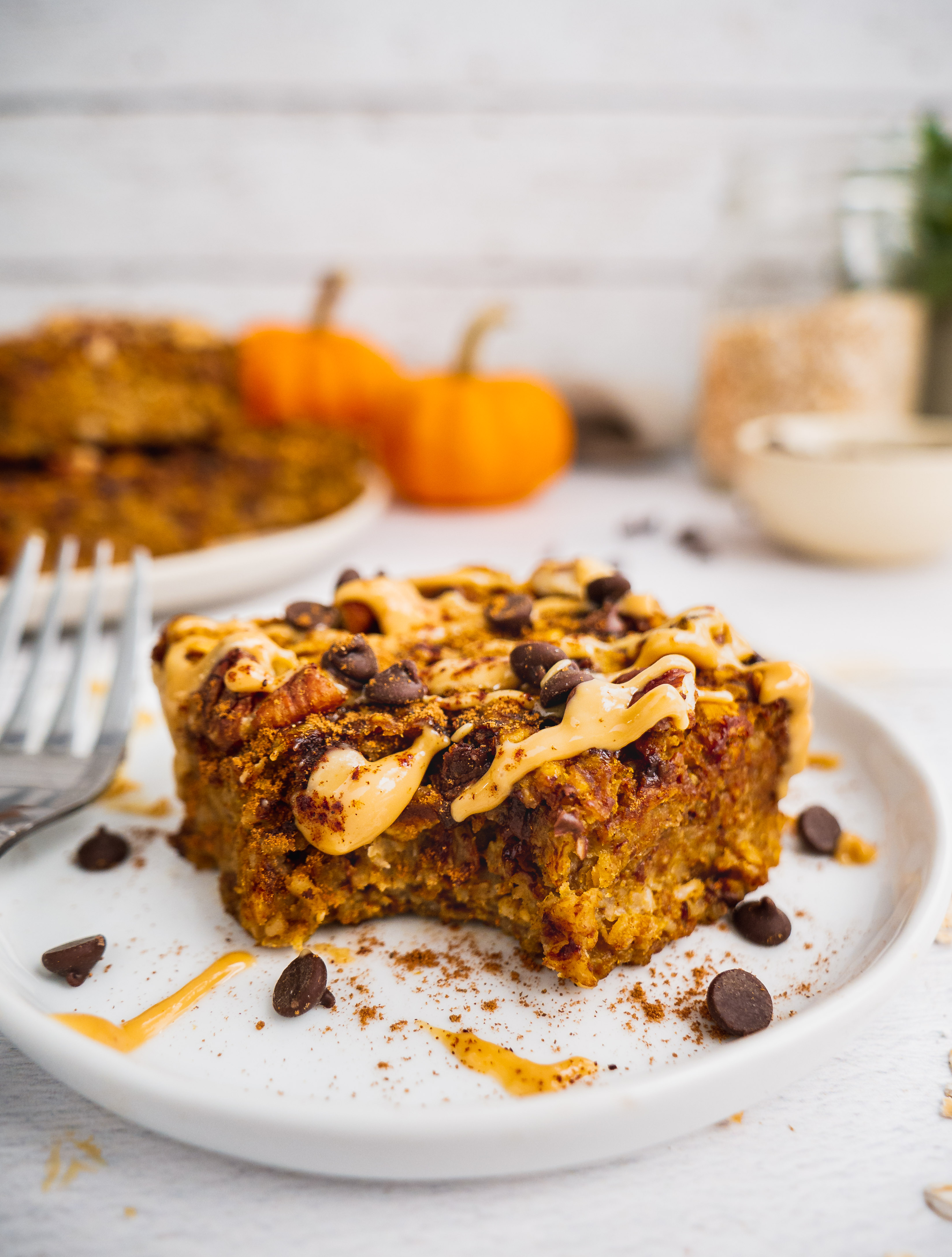 A piece of pumpkin oatmeal breakfast bars topped with peanut butter, chocolate chip and cinnamon with a bite. In the background there are more bars and pumpkins and a jar of gluten free oats.