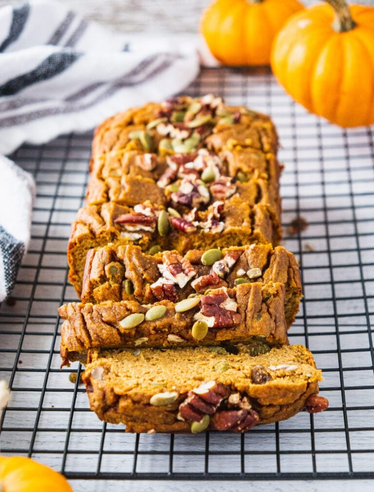 A loaf of sliced up healthy pumpkin bread topped with pumpkin seeds and pecans.