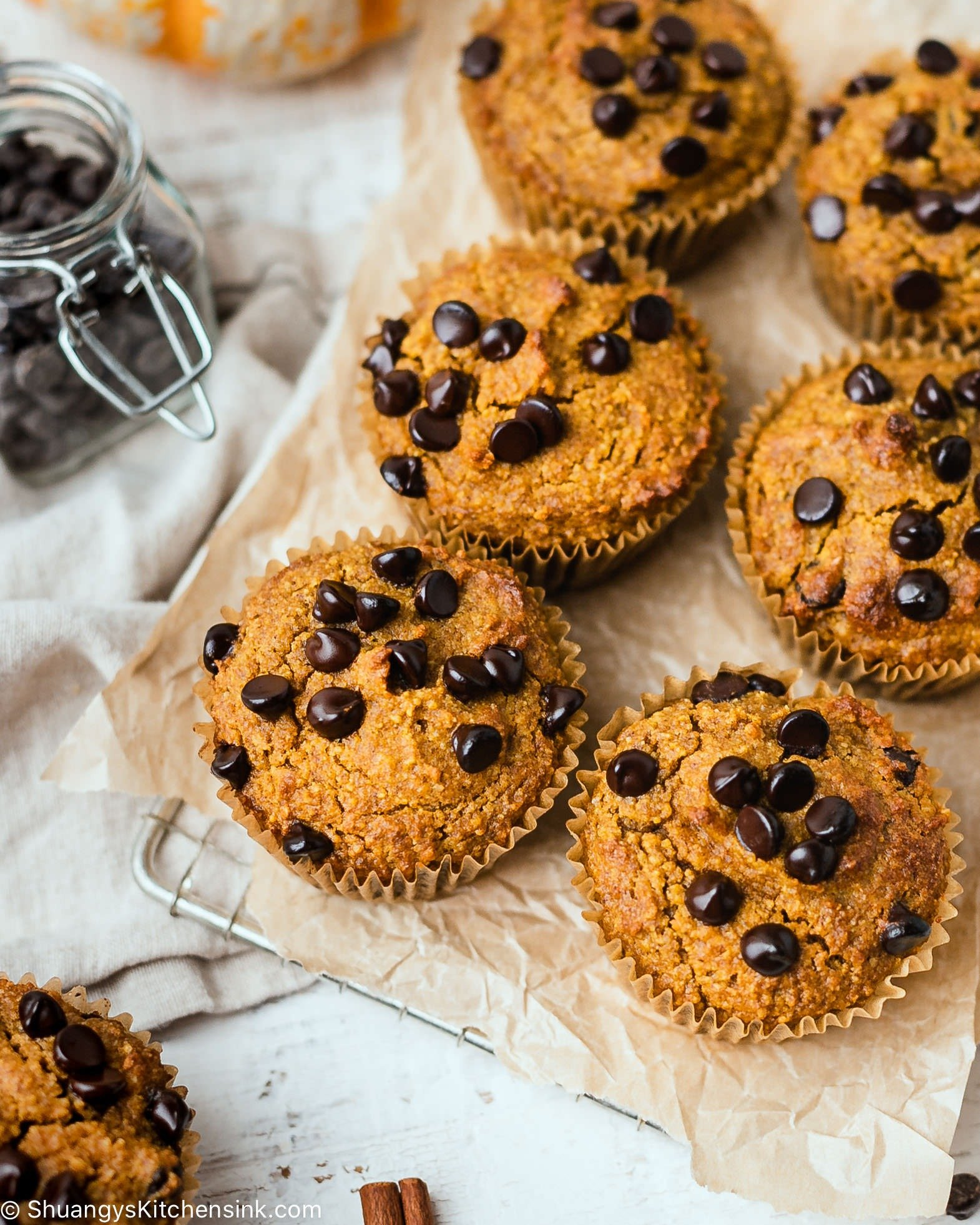 These are six paleo pumpkin muffins on a cooling rack. They are topped with dairy-free chocolate chis