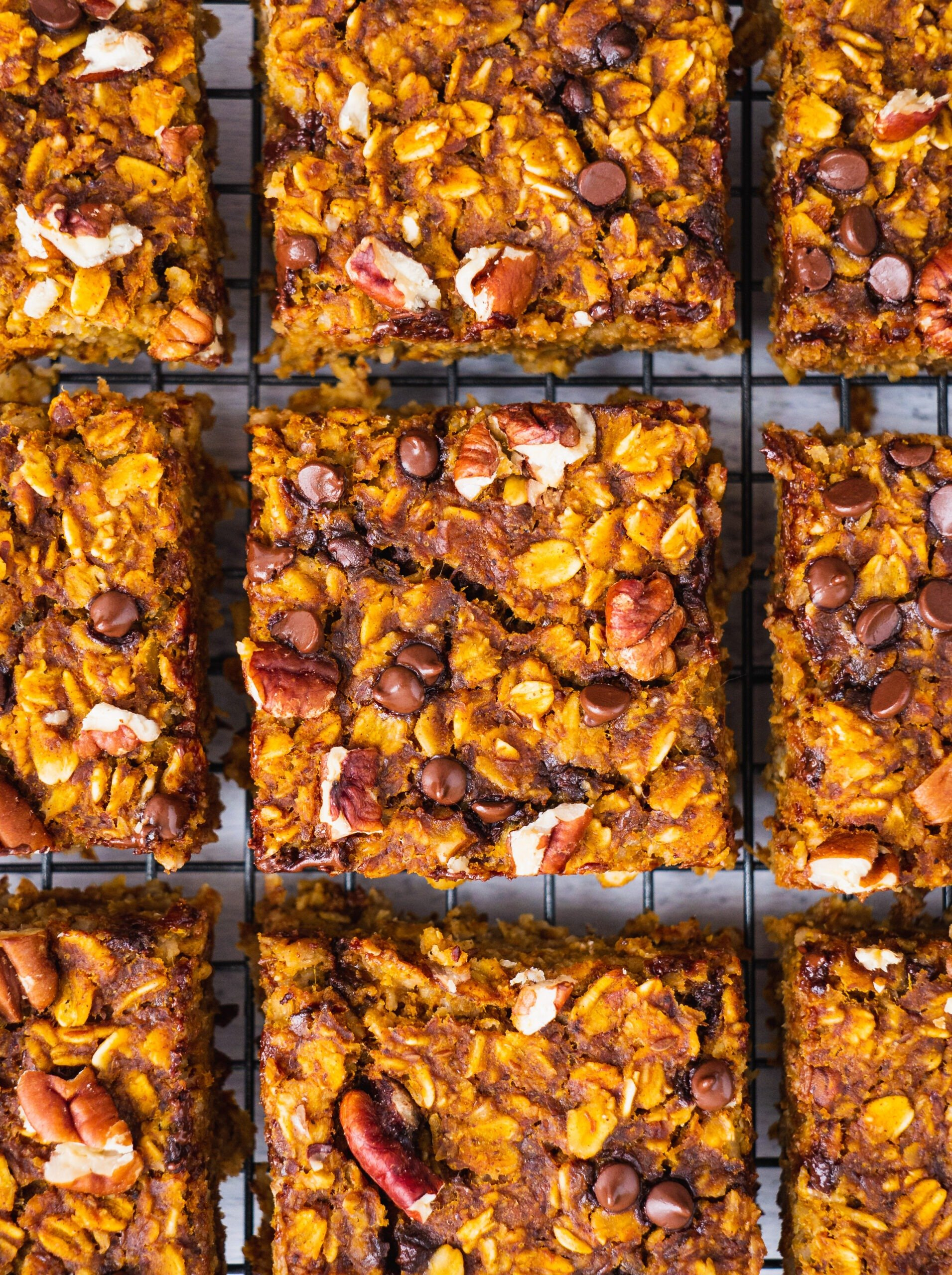 sliced up breakfast bars on a wire drying rack cooling.there are nuts and chocolate chips on top