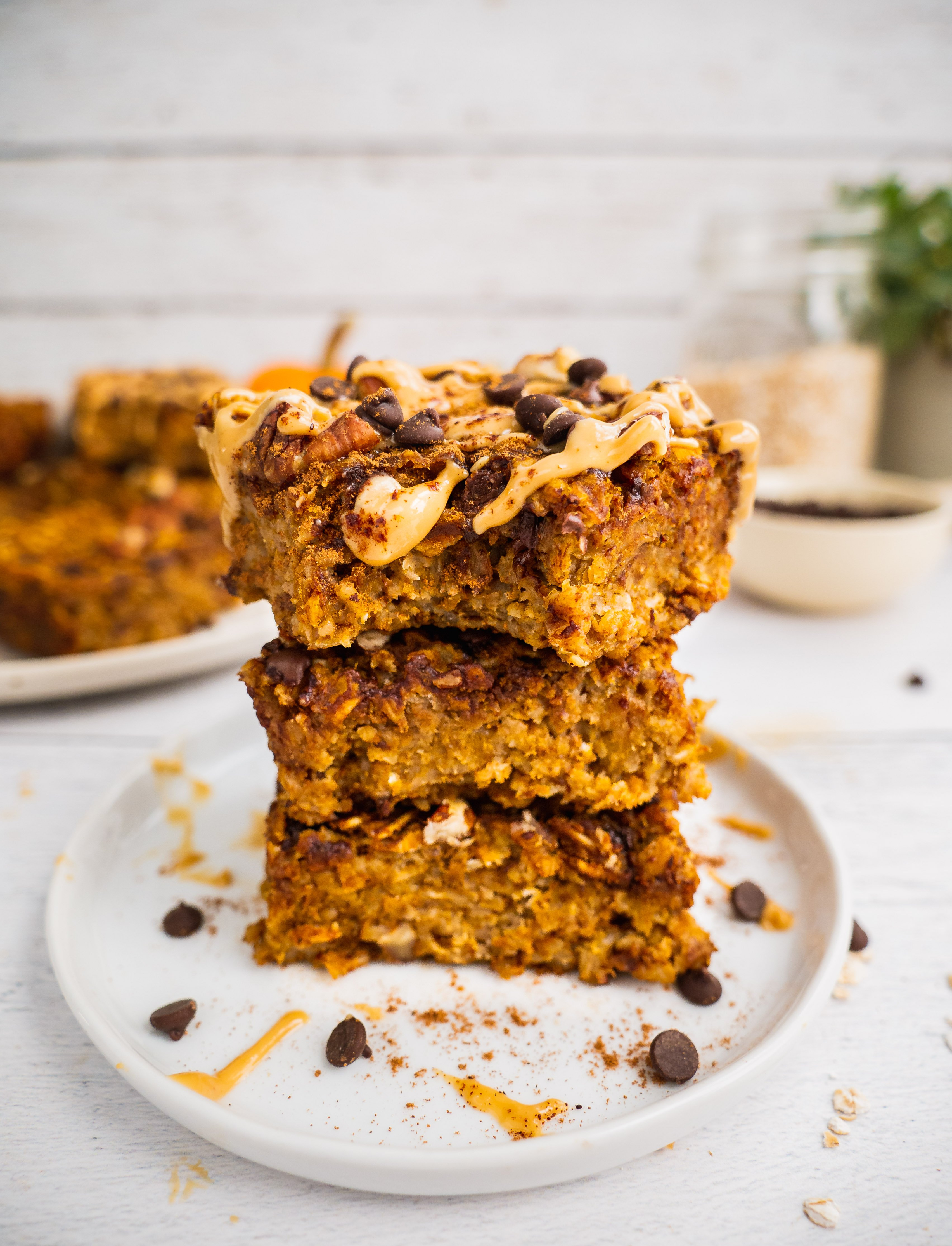 A stack of healthy pumpkin breakfast oatmeal bars topped with peanut butter (optional) and chocolate chip. The top one has a bite. In the background, there are more bars, a couple pumpkins and a jar of gluten free rolled oats.