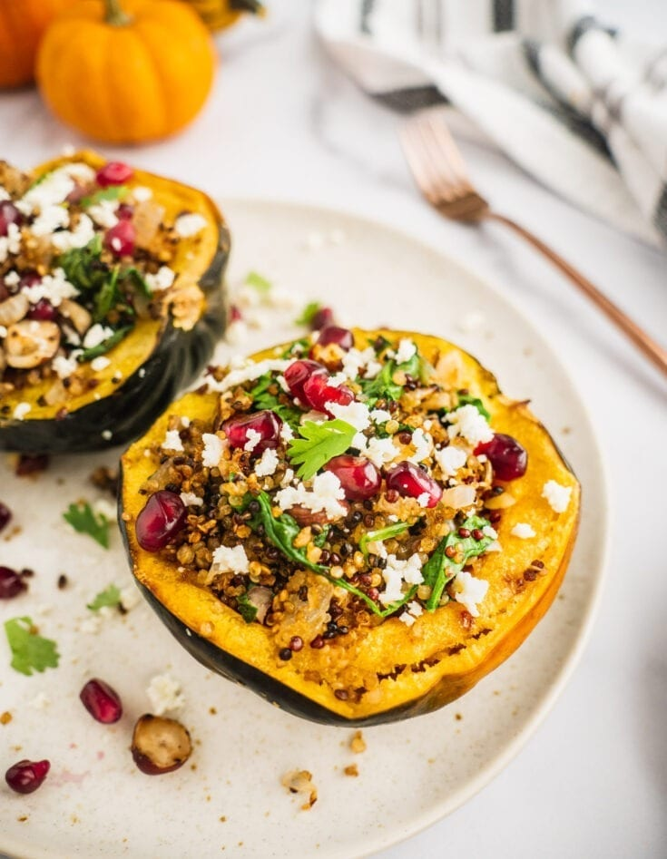 One roasted acorn stuffed with quinoa, onion, spinach and hazelnuts. Topped with avocado, pom seeds, and vegan cheese.